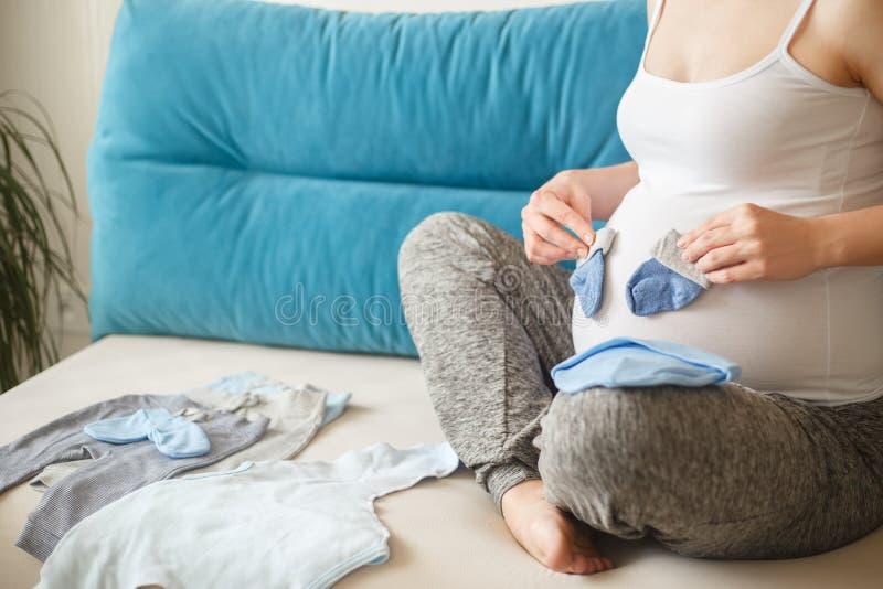 Mulher gravida que prepara a roupa do bebê fotos de stock