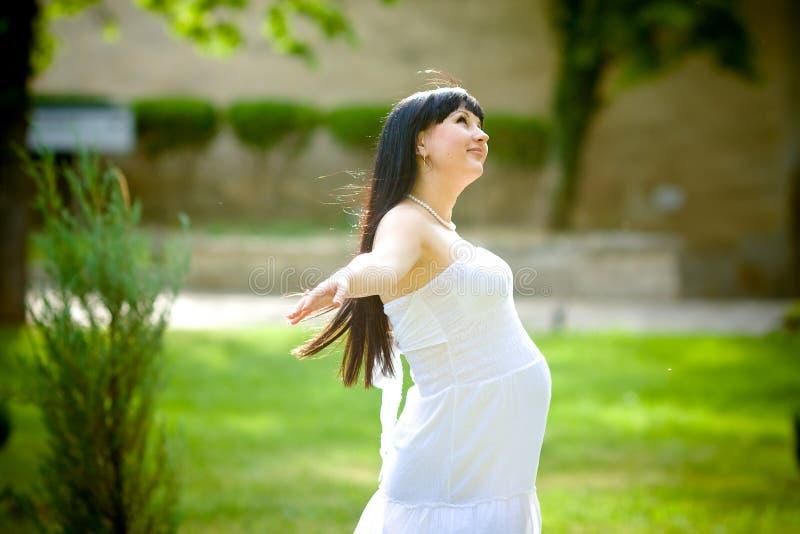 Mulher gravida que relaxa no parque imagens de stock