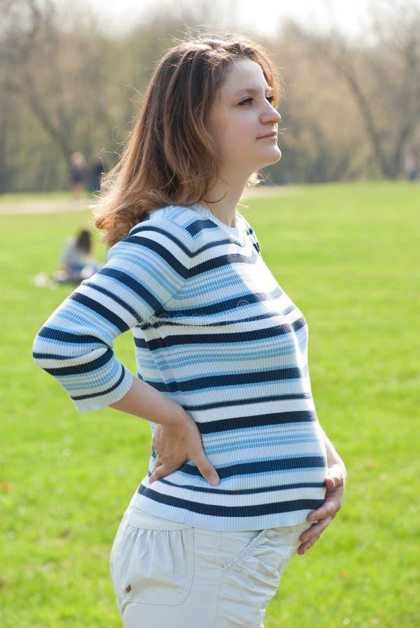 Mulher gravida que relaxa no prado imagens de stock