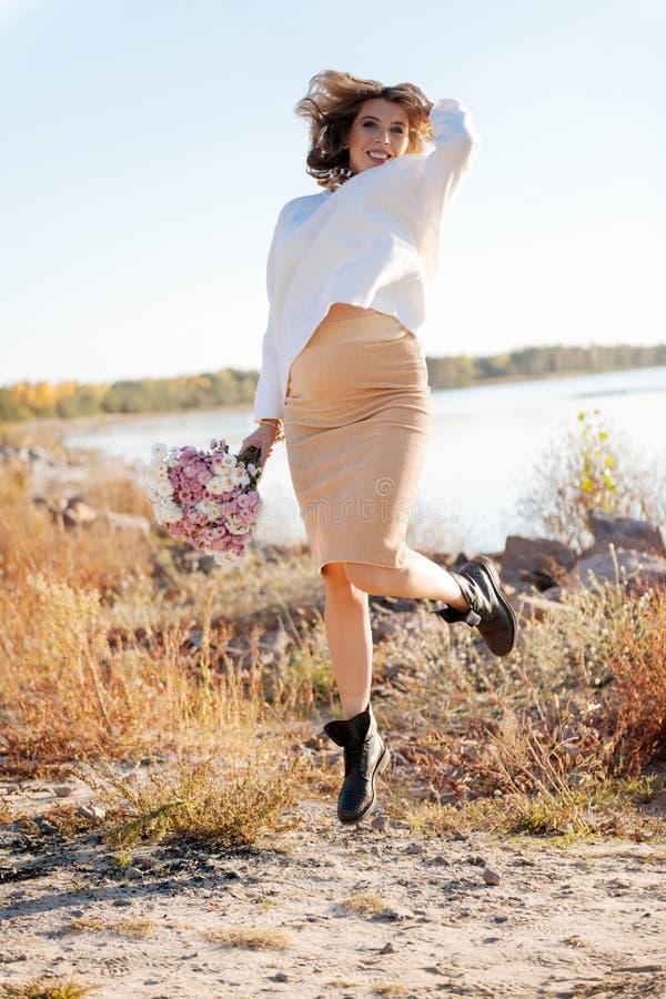 A mulher gravida que salta com um grupo de flores exteriores foto de stock royalty free