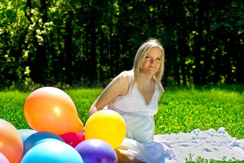 Mulher gravida que senta-se em baloons coloridos imagem de stock royalty free