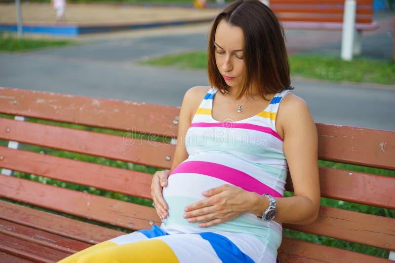 Mulher gravida que senta-se em um banco fotos de stock royalty free