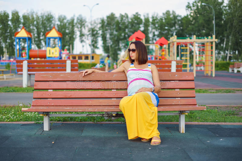 Mulher gravida que senta-se em um banco fotografia de stock royalty free
