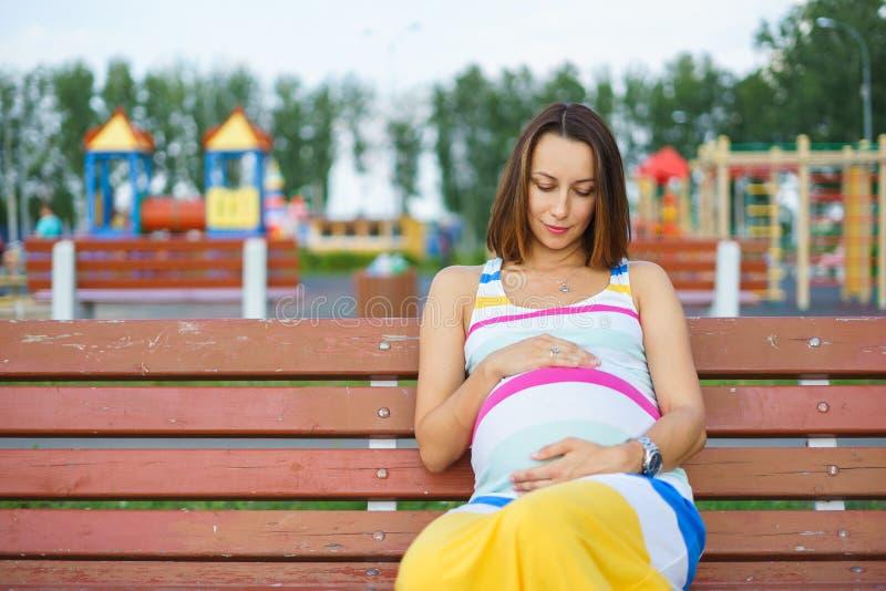 Mulher gravida que senta-se em um banco no campo de jogos imagens de stock royalty free