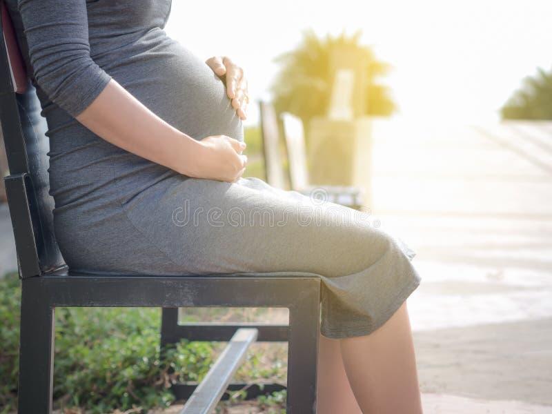 Mulher gravida que senta-se em um banco no parque Na manhã foto de stock royalty free
