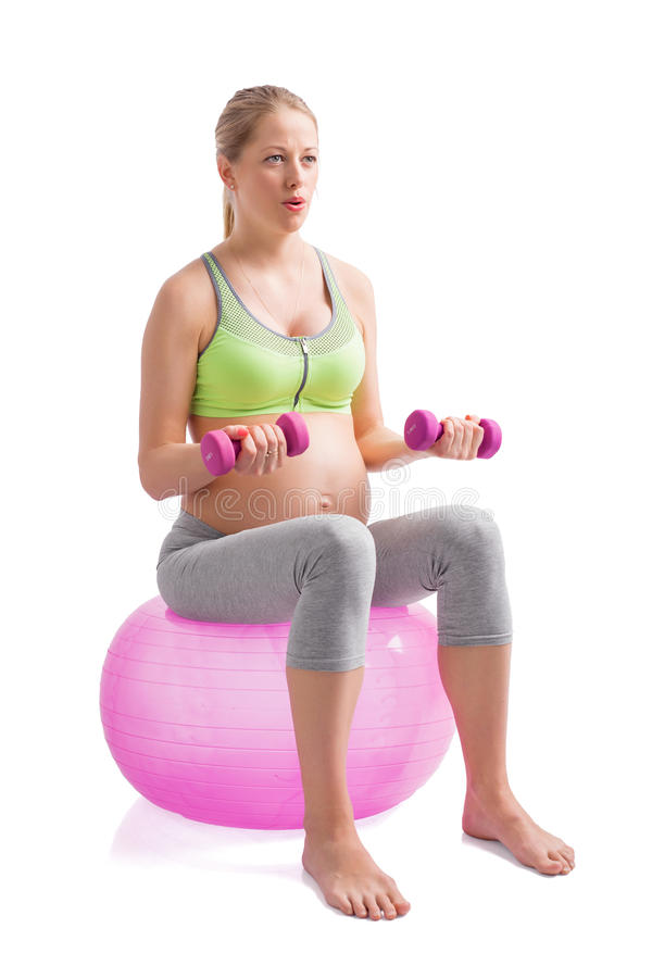 Mulher gravida que senta-se na bola de medicina imagens de stock royalty free