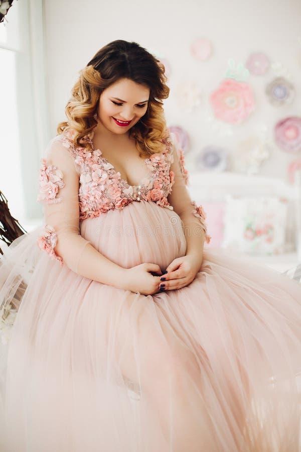 Mulher gravida que senta-se na grinalda decorada grande da videira fotos de stock royalty free