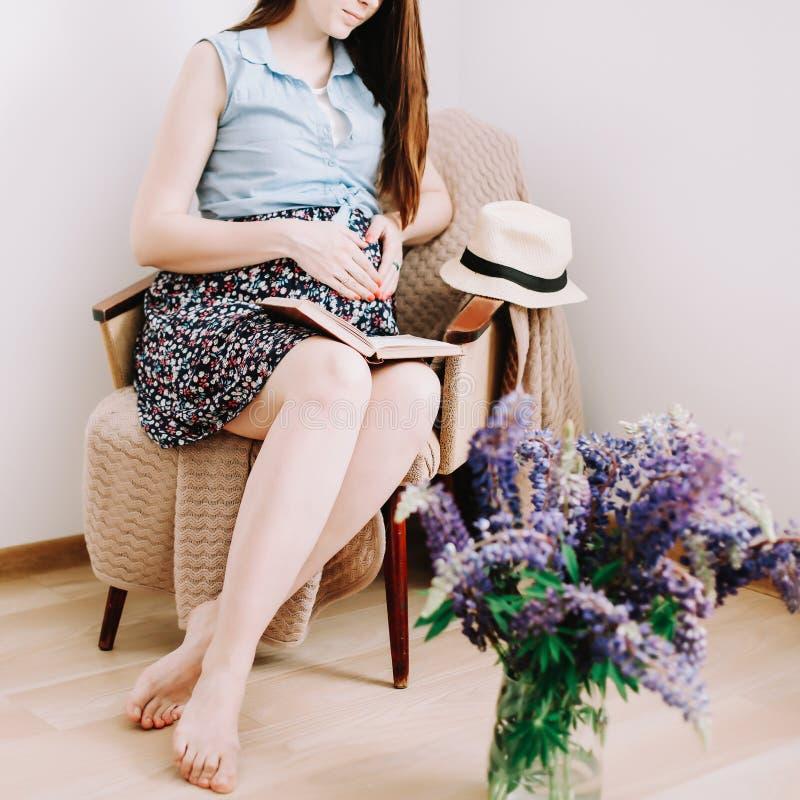 Mulher gravida que senta-se na poltrona em casa Conceito da gravidez, da maternidade, da prepara??o e da expectativa imagens de stock royalty free