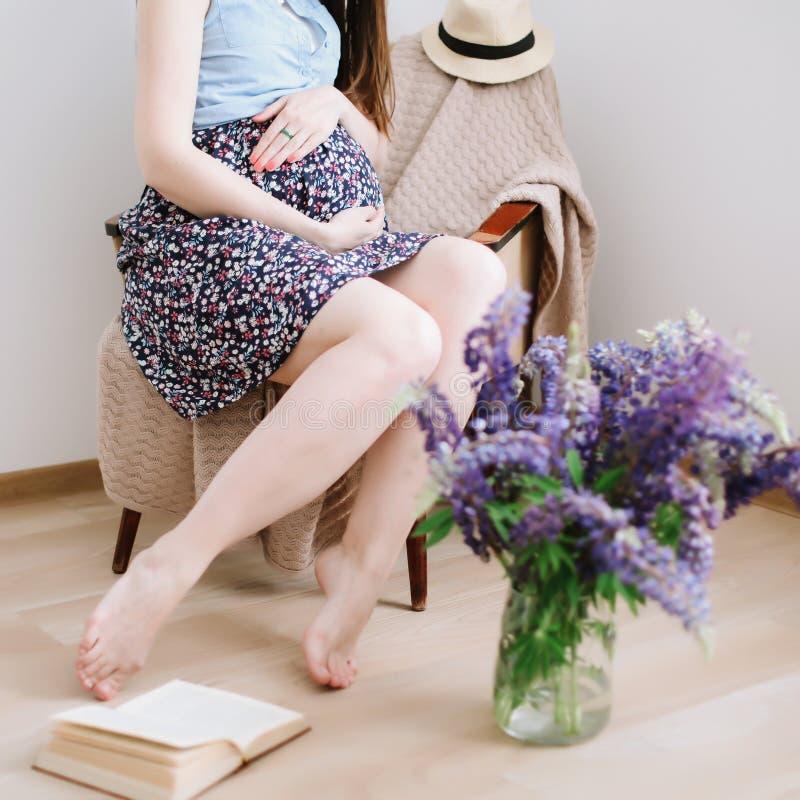 Mulher gravida que senta-se na poltrona em casa Conceito da gravidez, da maternidade, da prepara??o e da expectativa imagens de stock