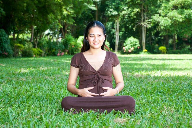 Mulher gravida que senta-se no parque em antecipação ao chil foto de stock royalty free