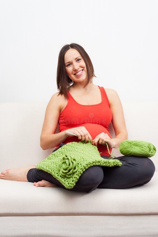 Mulher gravida que senta-se no sofá e em crocheting imagens de stock royalty free