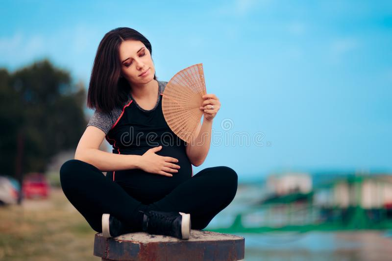 Mulher gravida que tem flashes quentes após o exercício imagem de stock