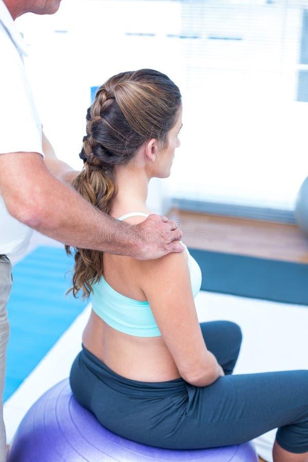 Mulher gravida que tem a massagem de relaxamento no gym fotos de stock royalty free