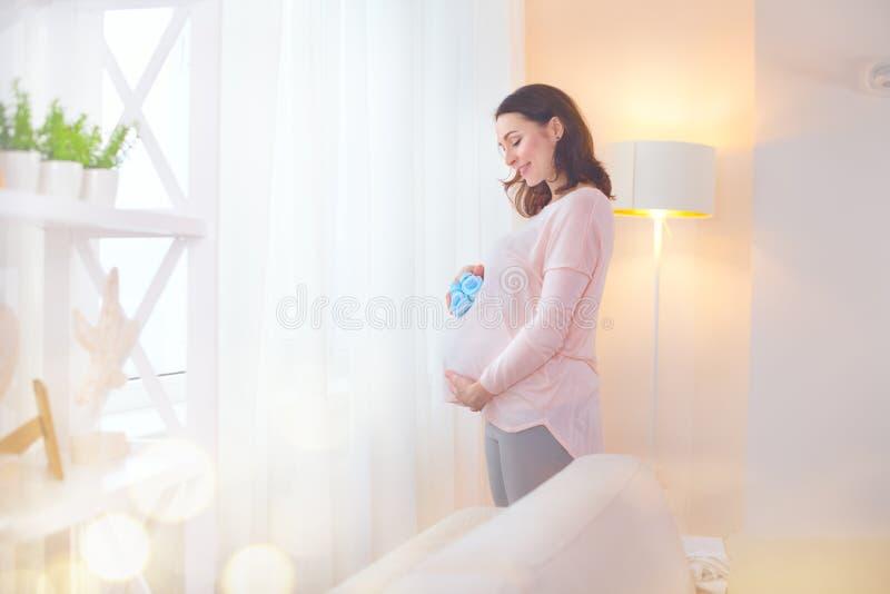 Mulher gravida que toca em sua barriga e que joga com as sapatas de bebê pequenas Meio grávido feliz mãe envelhecida em casa imagem de stock royalty free