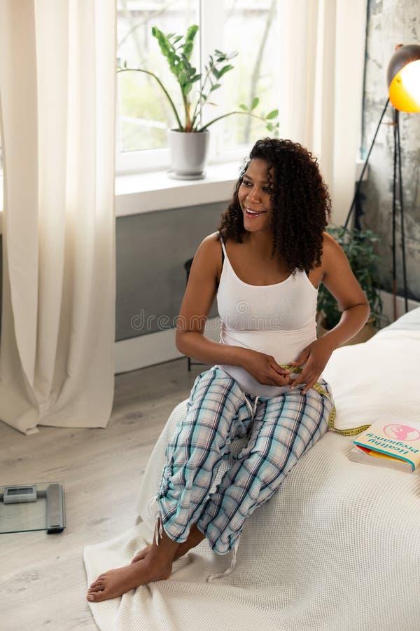 Mulher gravida que toma a medida de sua barriga imagens de stock royalty free