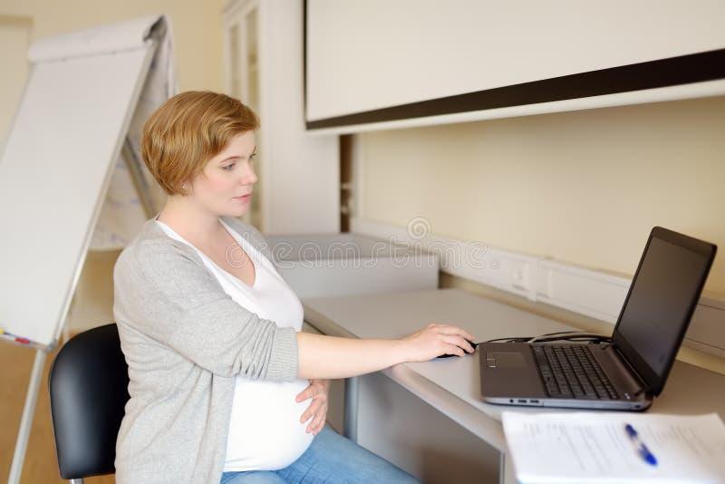 Mulher gravida que trabalha no portátil em seu lugar de trabalho no escritório Gravidez do seguro médico LICEN?AS DE PARTO Gravid foto de stock royalty free