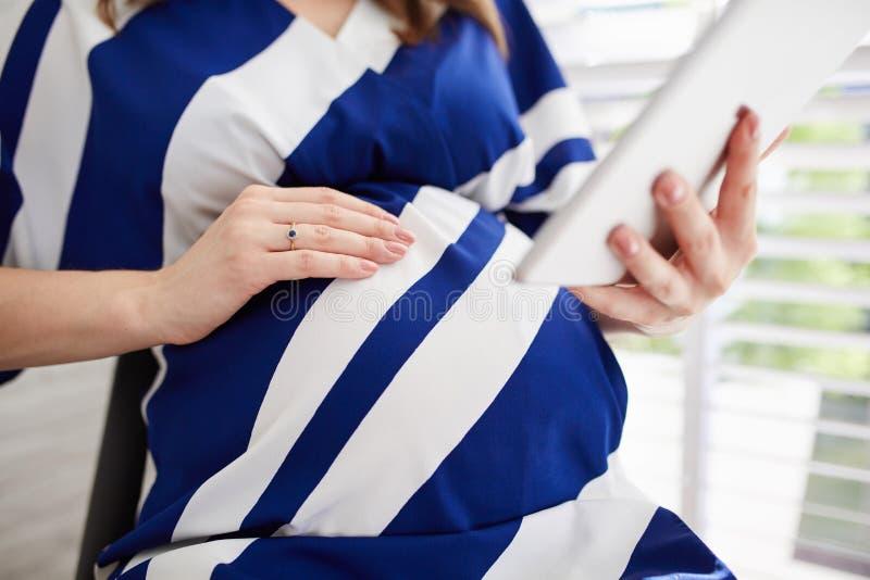 Mulher gravida que usa a tabuleta imagem de stock royalty free