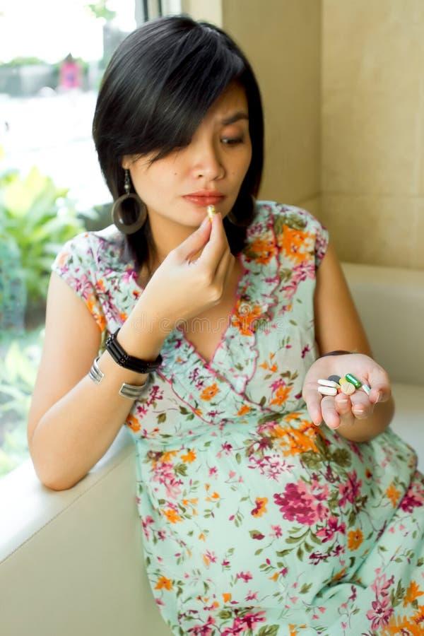 A mulher gravida toma vários comprimidos fotografia de stock