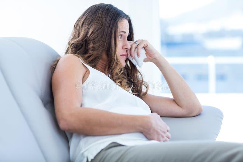 Mulher gravida triste que senta-se no sofá fotos de stock