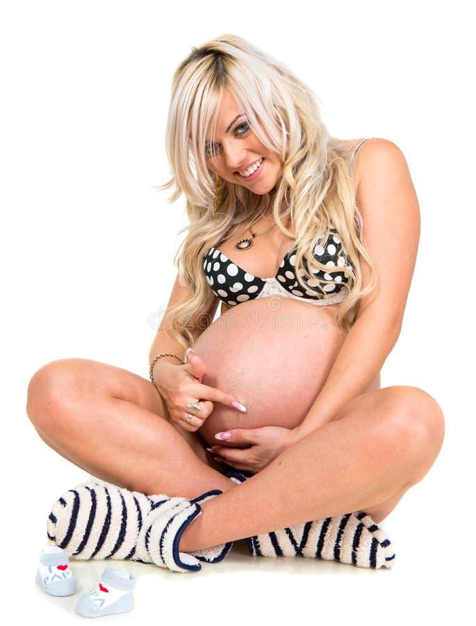 Mulher gravida um pares de sapatas de bebê fotos de stock royalty free