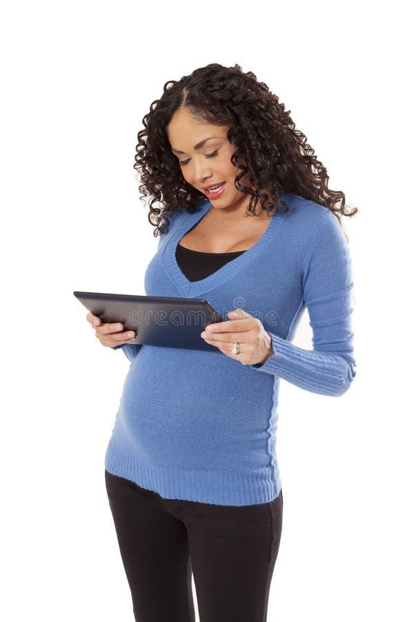 A mulher gravida usa um computador da tabuleta. fotos de stock