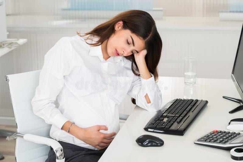 Mulher gravida virada que senta-se na mesa do computador imagens de stock royalty free