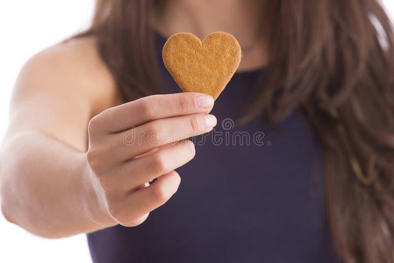 A mulher guarda a cookie dada forma coração foto de stock