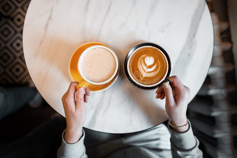 A mulher guarda dois copos de bebidas quentes Latte e cappuccino saborosos quentes nas mãos fêmeas Para o almoço a pausa para o c fotos de stock