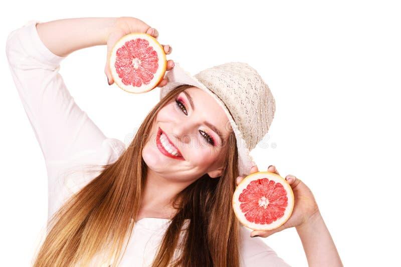 A mulher guarda dois halfs de citrinos da toranja nas m?os imagem de stock royalty free