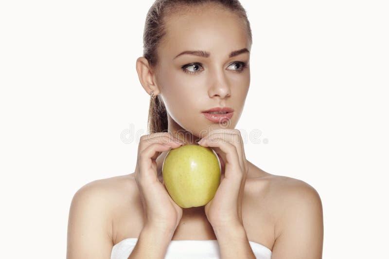 A mulher guarda a maçã verde grande na frente de sua cara fotos de stock royalty free