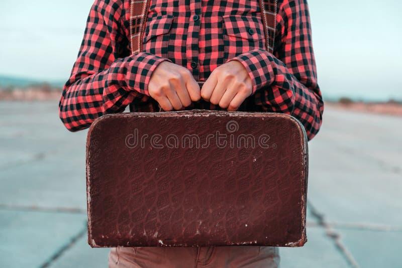 A mulher guarda a mala de viagem retro pequena fotografia de stock
