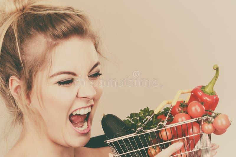 A mulher guarda o cesto de compras com vegetais fotos de stock royalty free