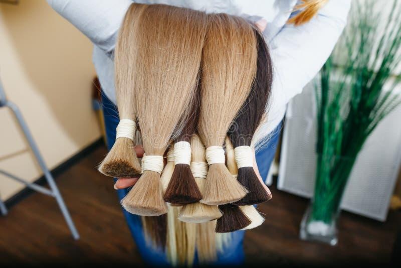 A mulher guarda o equipamento da extensão do cabelo do cabelo natural Amostras do cabelo de cores diferentes fotografia de stock