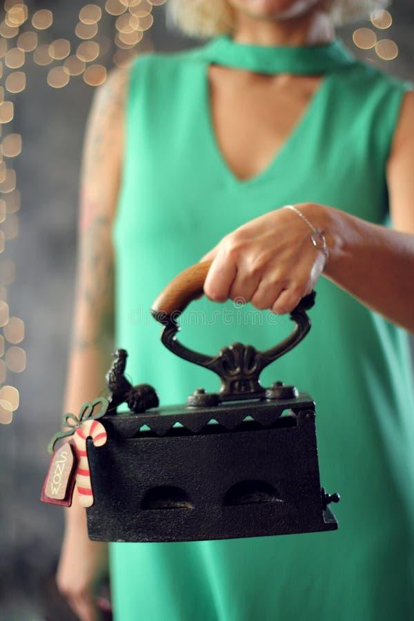 A mulher guarda o ferro velho com um brinquedo do Natal Estilo retro em um boke imagens de stock