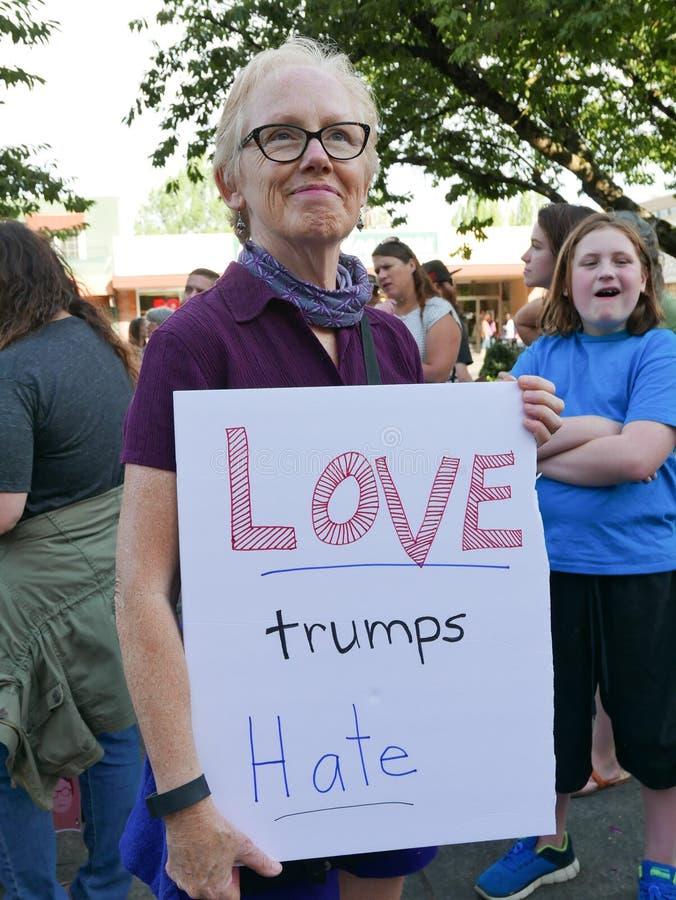 A mulher guarda o sinal do ` do ódio dos trunfos do AMOR do ` na reunião política foto de stock