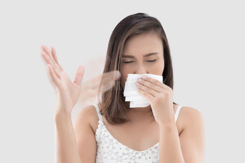 A mulher guarda o tecido cobre seu nariz porque cheira o mau imagens de stock