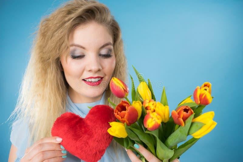 A mulher guarda tulipas e o cora??o vermelho foto de stock