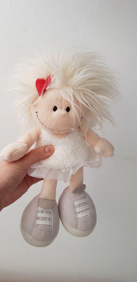 A mulher guarda um brinquedo macio do anjo foto de stock