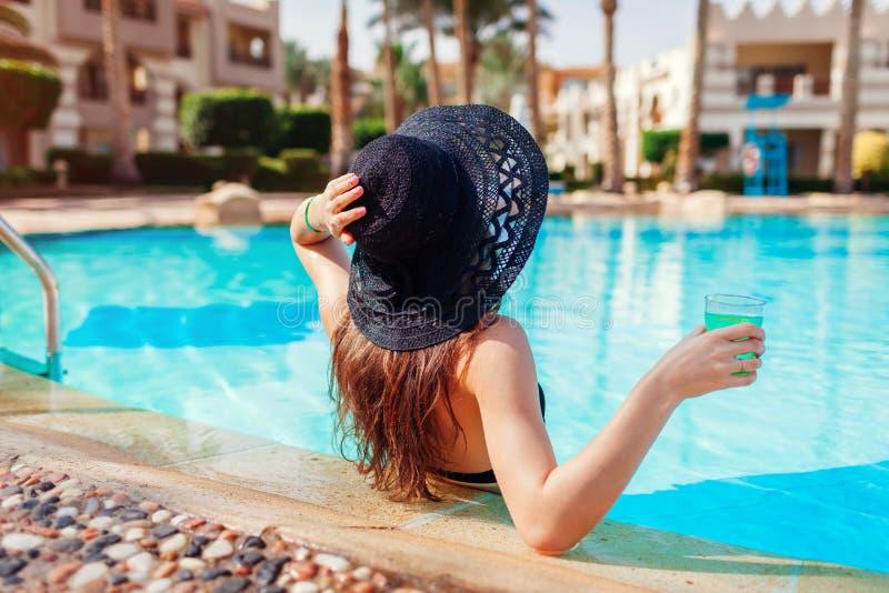 A mulher guarda um cocktail na piscina do hotel Férias de verão Toda inclusivo fotografia de stock