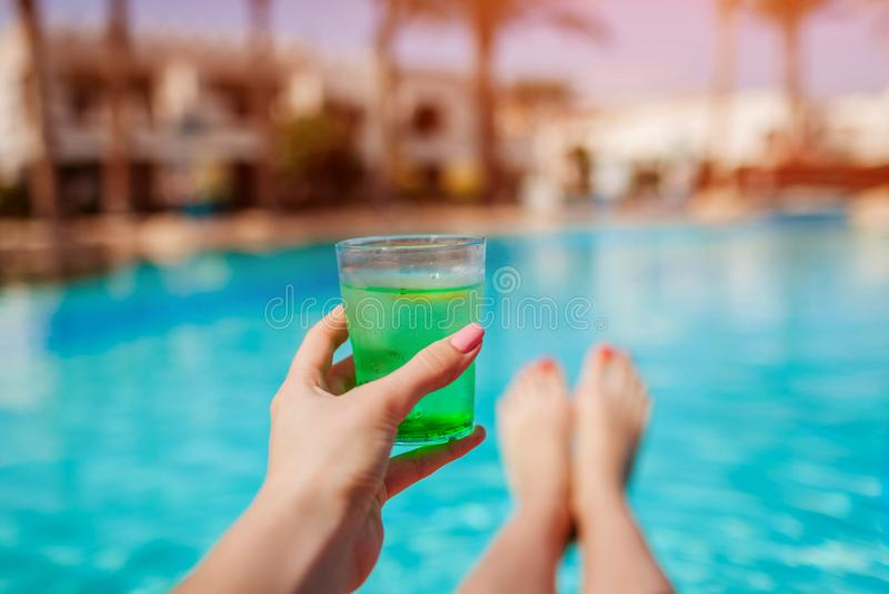 A mulher guarda um cocktail no fundo da piscina Toda inclusivo foto de stock royalty free
