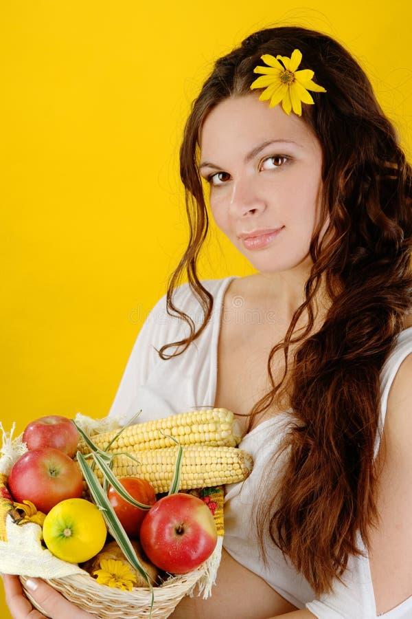 A mulher guarda uma cesta das frutas e legumes olhando a câmera fotografia de stock royalty free
