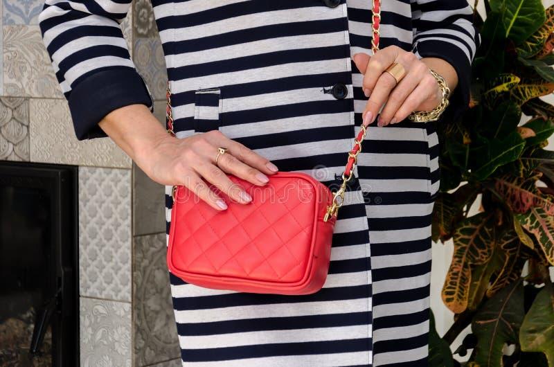 A mulher guarda uma embreagem à moda pequena do saco da sagacidade brilhante da cor vermelha foto de stock royalty free