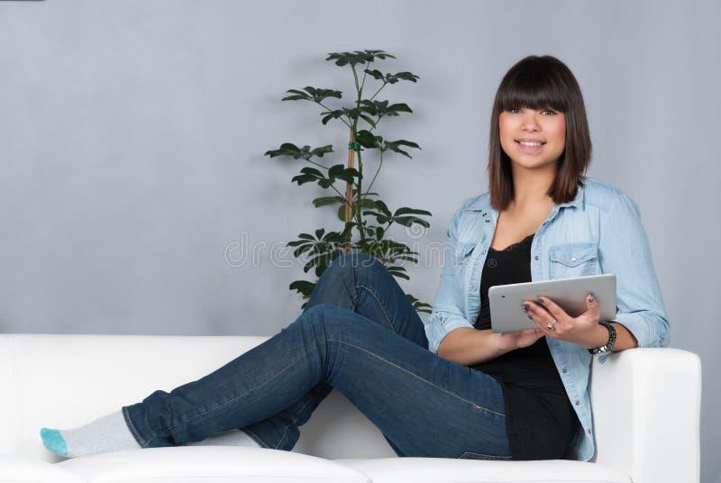 A mulher guarda uma tabuleta foto de stock