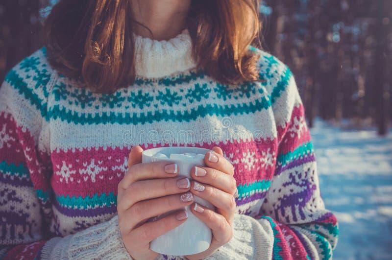 A mulher guarda a xícara de café com o marshmallow na floresta do inverno imagem de stock
