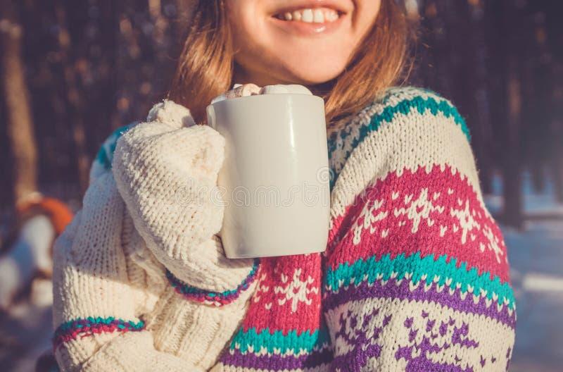 A mulher guarda a xícara de café com o marshmallow na floresta do inverno imagens de stock