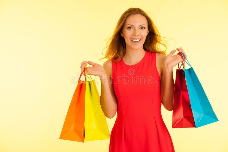 Mulher haapy nova bonita no vestido vermelho vibrante que guarda sacos de compras sobre o fundo amarelo imagem de stock