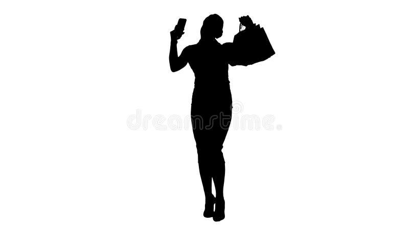 Mulher heerful do ¡ da silhueta Ð com os sacos de compras que tomam o selfie foto de stock
