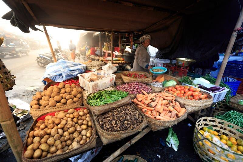 A mulher hindu do Balinese vende o produto local fresco em seu vendedor para o dinheiro muito pequeno foto de stock royalty free
