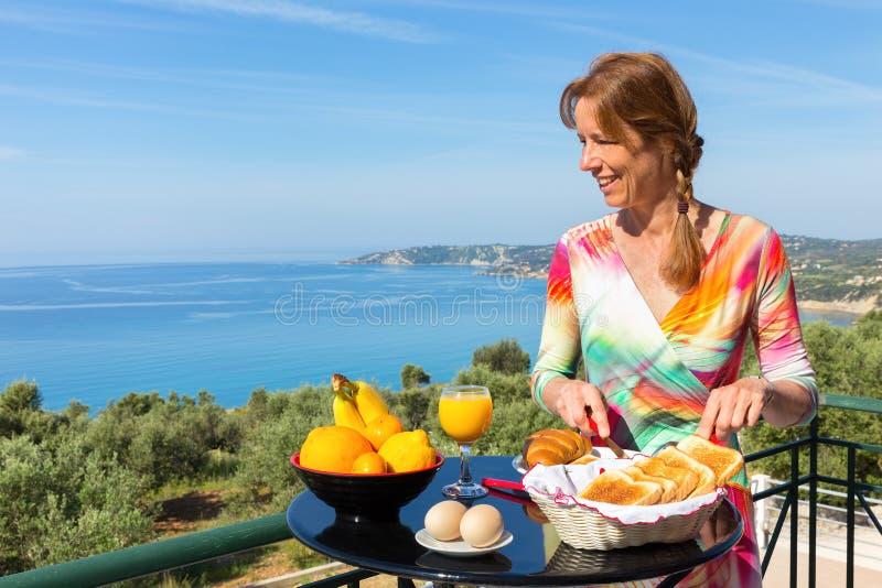 Mulher holandesa que come o café da manhã com fundo do mar imagem de stock royalty free