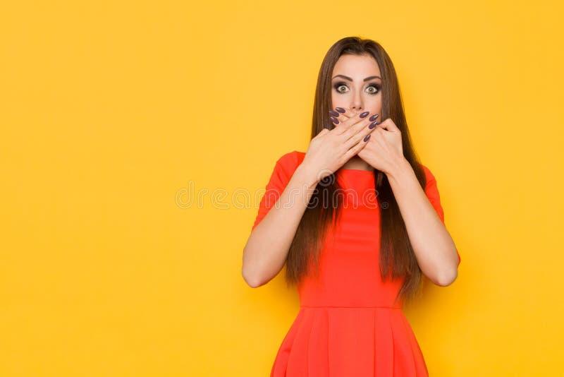 A mulher horrorizada bonita está fechando sua boca com mãos fotografia de stock royalty free